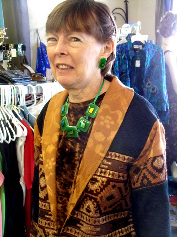 Ann sets off brown with a five-piece green fused glass necklace with varied dichroic glass in the center matching earrings