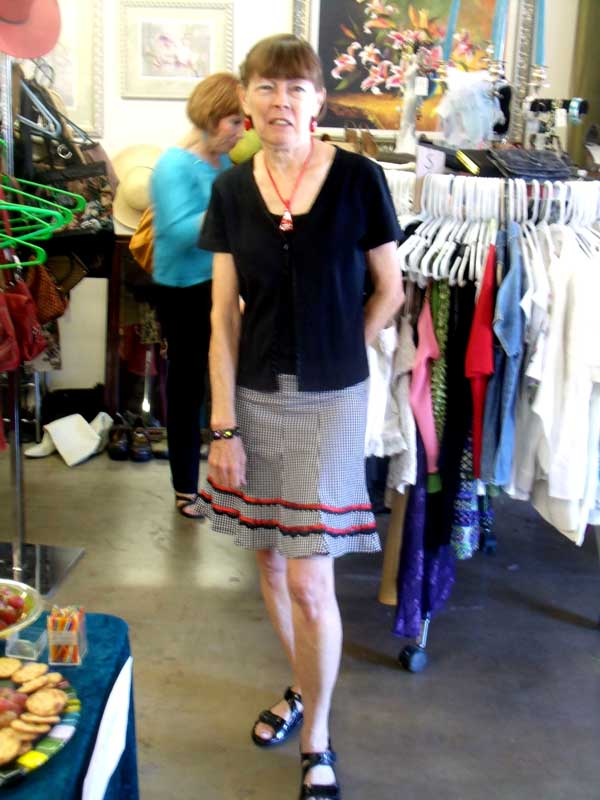 Ann, in black and white skirt, trimmed in red and black, and black top. The red is brought out by a bright red fused glass pendant and matching earrings.