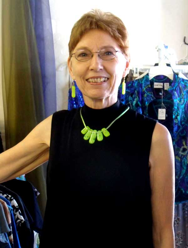 Bonnie, up close, in a black top and small five-piece lime green fused glass necklace and matching earrings