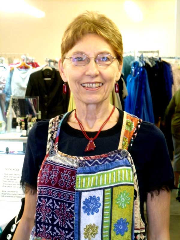Bonnie relaxes in a dark blue blouse and multicolored overalls, set off by a dark red fused glass pendant and matching earrings.
