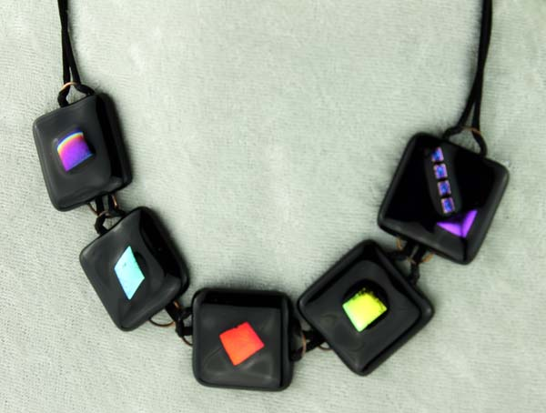 5-pc fused glass necklace, black glass with varied dichroic centers black cord with matching fob to hold it on, $70.00